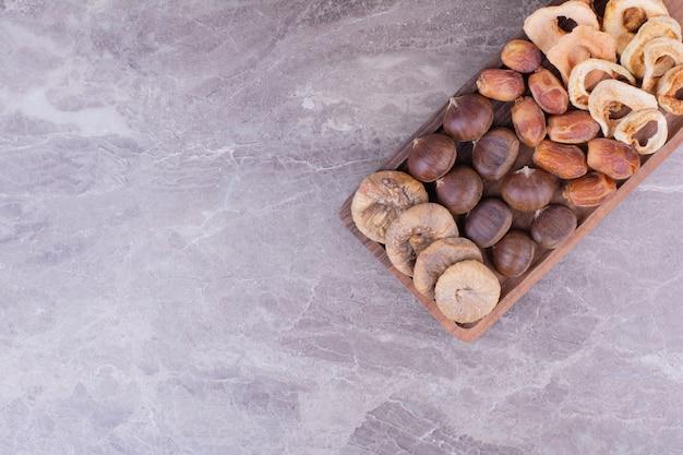 Trockene früchte auf einer holzplatte auf dem stein
