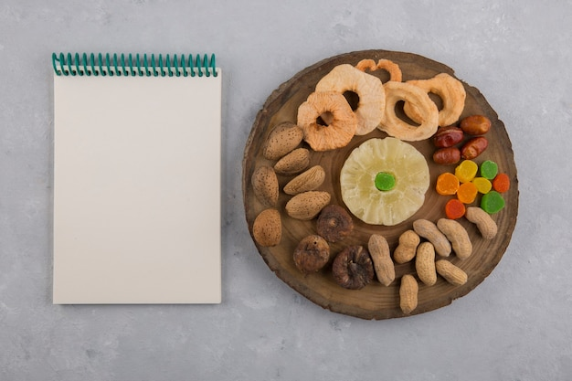 Trockene früchte und snacks auf einer holzplatte mit einem notizbuch beiseite
