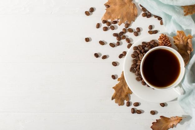 Trockene gelbe blätter, blauer schal, kaffeebohnen und eine schale auf einer weißen tabelle, morgenanfangstag. herbststimmung hintergrund, exemplar, flache lage.