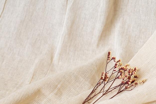 Trockene gelbe blume auf natürlichem baumwollgewebehintergrund