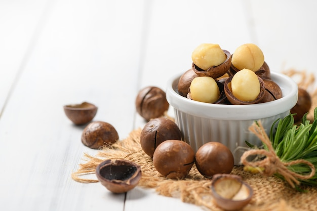 Trockene geröstete macadamia-nuss in der weißen tasse auf weißem holzhintergrund,