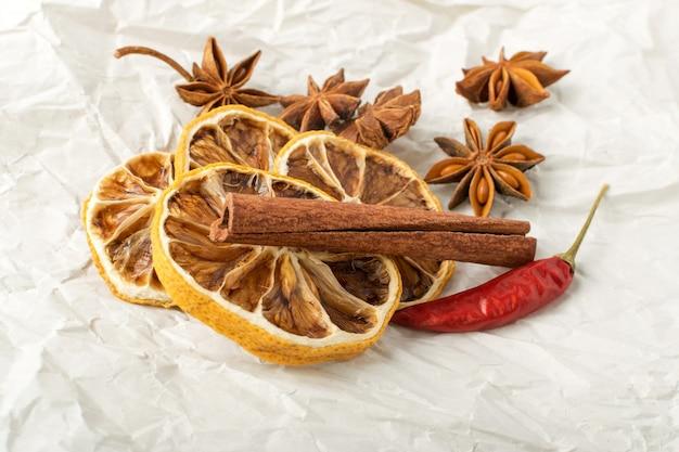 Trockene gewürze für glühwein mit dehydrierten geschnittenen zitrusfrüchten auf vintage-kraftpapier