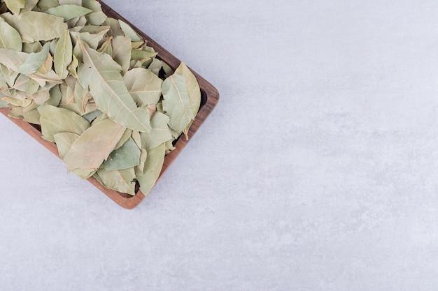 Trockene grüne lorbeerblätter auf einer platte auf konkretem hintergrund. foto in hoher qualität
