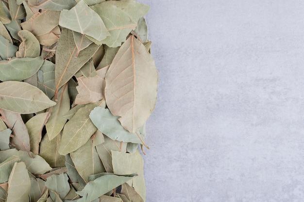 Trockene grüne lorbeerblätter auf konkretem hintergrund. foto in hoher qualität
