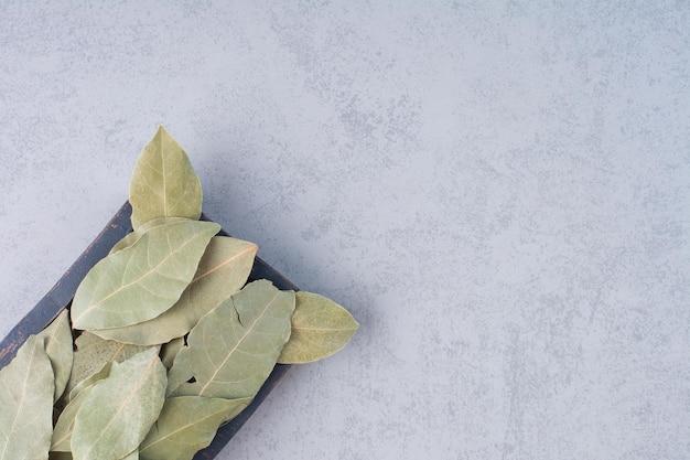 Trockene grüne lorbeerblätter auf konkretem hintergrund.