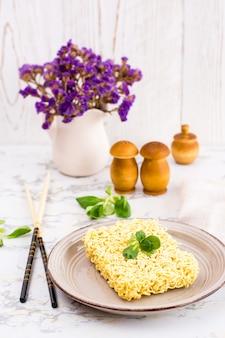 Trockene indische nudeln mit salatblättern auf keramikplatte und essstäbchen