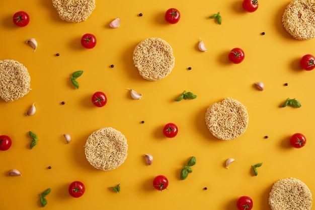 Trockene instantnudeln mit tomaten, knoblauch, basilikum und pfeffer für die zubereitung von frischer suppe, gelber hintergrund. vorbereitung des qucik-mittagessens. ungesundes essen und fast-food-konzept. zutaten für die zubereitung von gerichten