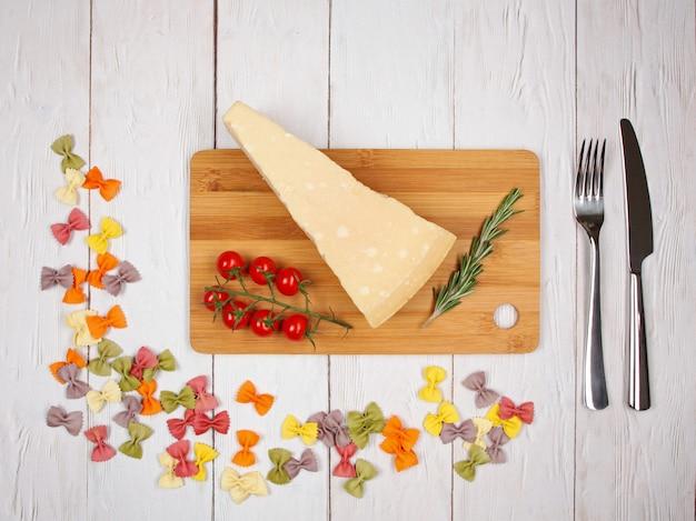 Trockene italienische pasta farfalle mit tomaten, käse, rosmarin, gabel und messer auf hellem hölzernem hintergrund. mit kopierplatz