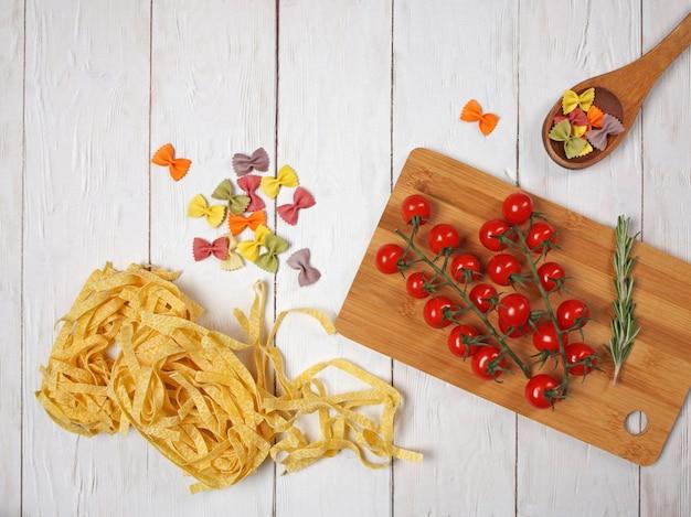 Trockene italienische pasta fettuccini und farfalle mit tomaten und rosmarin auf hellem holzhintergrund