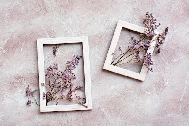 Trockene lila blumen in zwei weißen holzrahmen auf einem strukturierten hintergrund. romantische gruß-vintage-karte. ansicht von oben