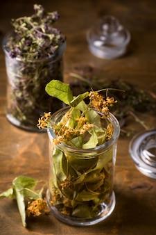 Trockene lindenblumen in einem glas, draufsicht