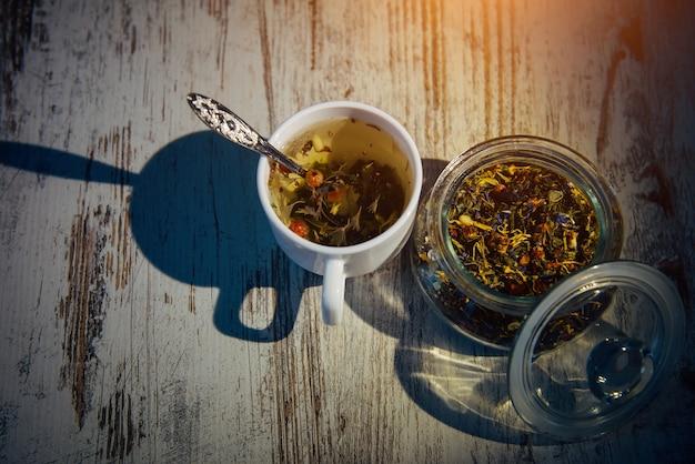 Trockene mischung aus teeblättern, kräutern, blütenblättern, beeren und nüssen in glasschüssel. natürlicher kräutertee in weißer tasse auf grauem holzhintergrund im abendlicht, schatten auf dem tisch.