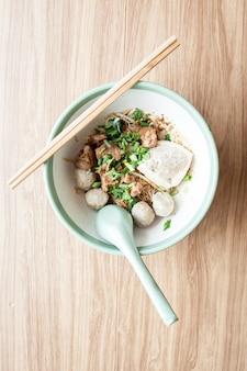 Trockene nudelschweinefleischfleischklöschen und -tofu der reissuppennudeln mit schweinefleisch und essstäbchen und löffel