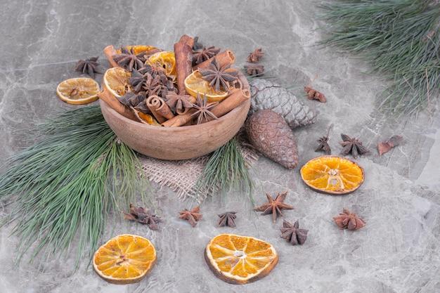 Trockene orangenscheiben mit anis in einer holzschale.