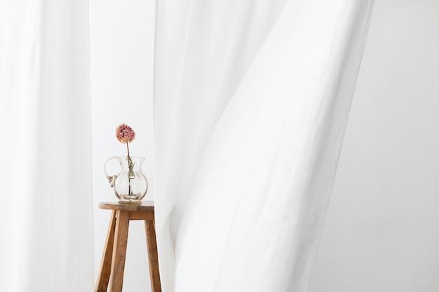 Trockene pfingstrosenblume in einem glaskrug auf einem hölzernen hocker in einem weißen raum