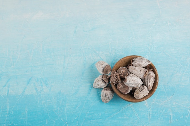 Trockene pflaume datiert in einer hölzernen untertasse auf blauem raum