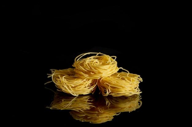 Trockene, rohe eiernudeln capelli, lokalisiert auf schwarzem hintergrund.