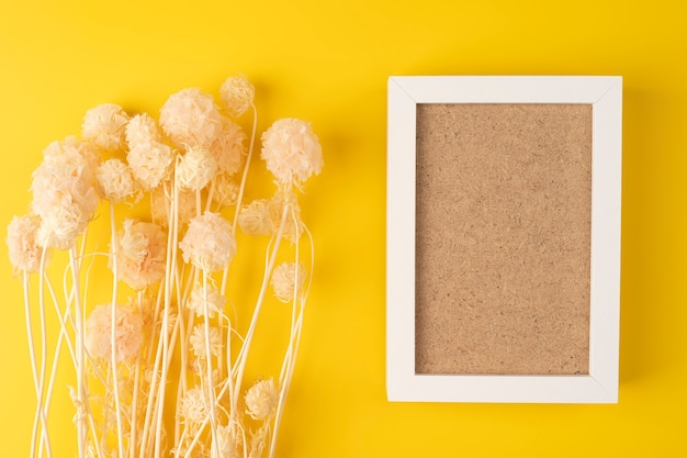 Trockene rosa blüten auf gelber oberfläche von oben mit platz für text auf einem rahmen draufsicht geschossen