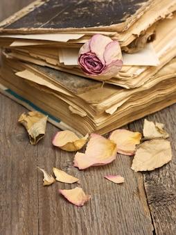 Trockene rose und alte bücher auf hölzernem hintergrund