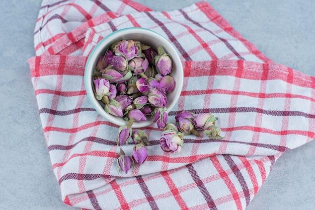 Trockene rosenblüte in der schüssel auf handtuch auf marmor.