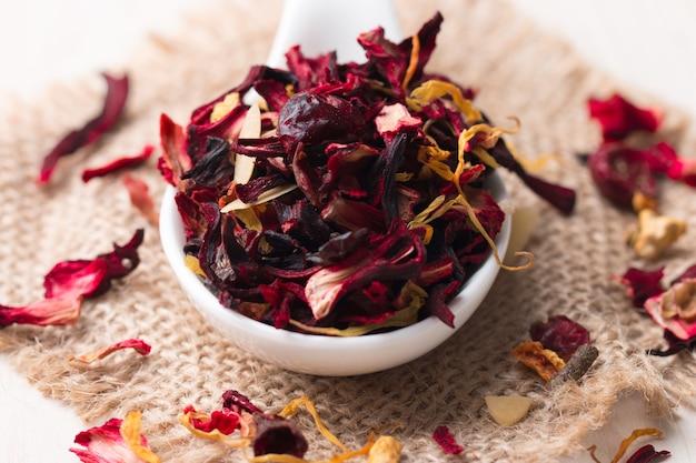 Trockene rote blumenfrucht und kräuter-hibiskus-tee mit blütenblättern