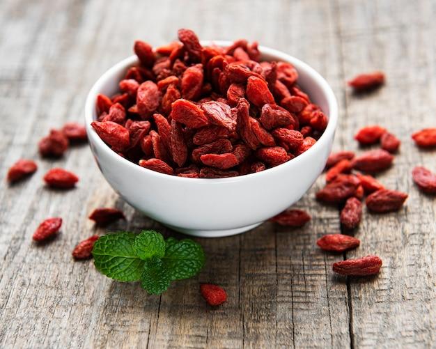 Trockene rote goji-beeren für eine gesunde ernährung auf einer alten holzoberfläche