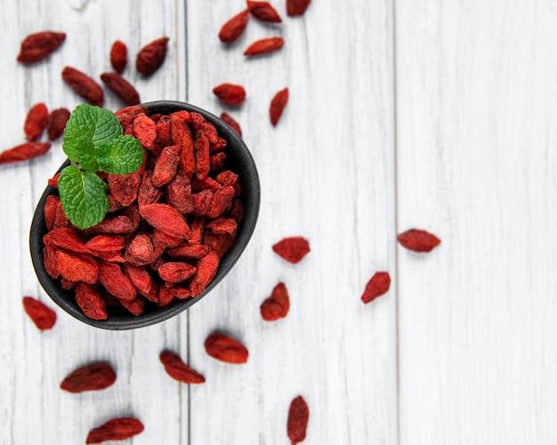 Trockene rote gojibeeren für eine gesunde ernährung auf altem holzhintergrund