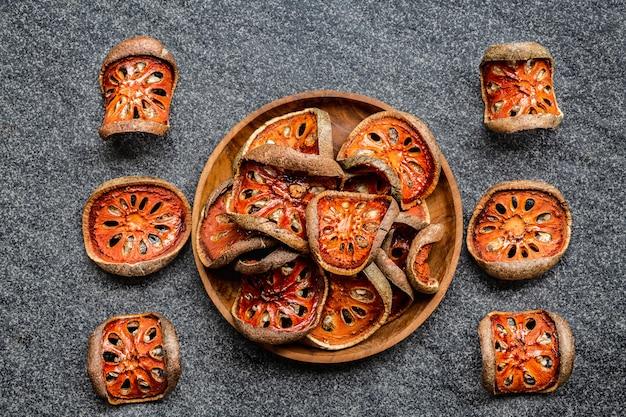 Trockene scheiben von bael-früchten in der holzschale