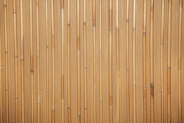 Trockene schilfbeschaffenheit. bio-naturtapete aus gelbem zuckerrohr. natürlicher warmer hölzerner hintergrund mit bambus und stroh