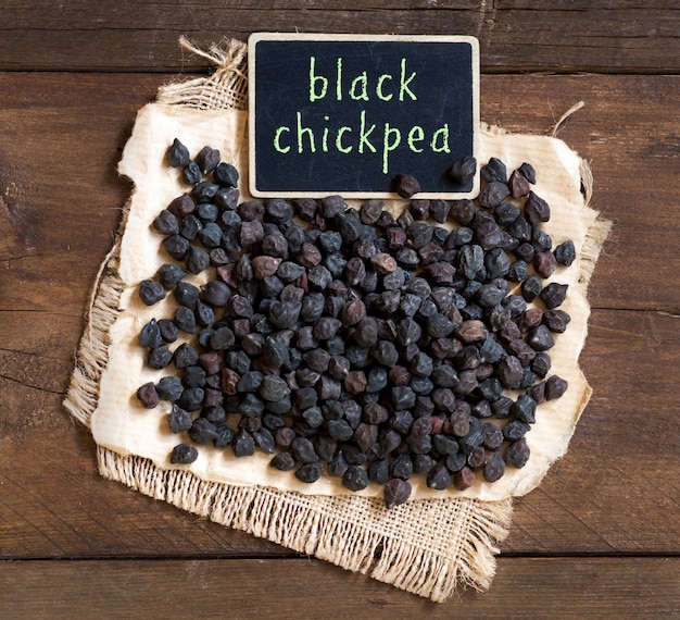 Trockene schwarze kichererbse mit einer kleinen tafel auf brauner hölzerner tischoberansicht