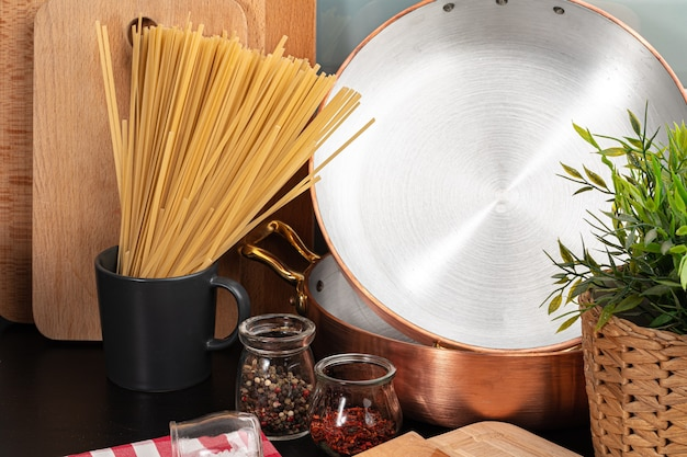 Trockene spaghetti auf einer küchentheke mit kochutensilien schließen