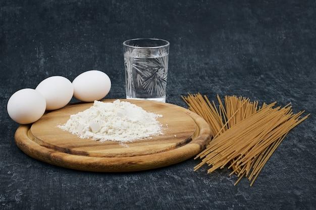 Trockene spaghetti, mehl auf einem holzbrett, hühnereier und ein glas wasser
