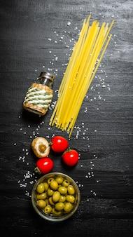 Trockene spaghetti mit oliven, tomaten und salz. auf einem schwarzen holztisch. draufsicht