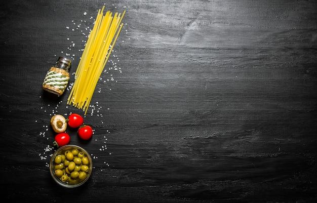 Trockene spaghetti mit oliven, tomaten und salz. auf einem schwarzen holztisch. freier platz für text. draufsicht