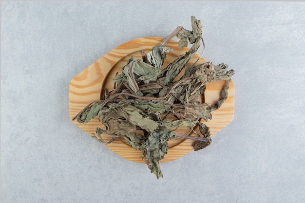 Trockene teeblätter auf holzplatte.