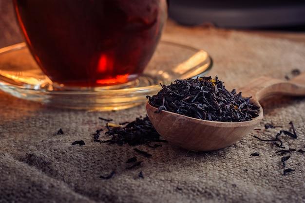 Trockene teeblätter in einem holzlöffel und in einer glastasse tee gebraut