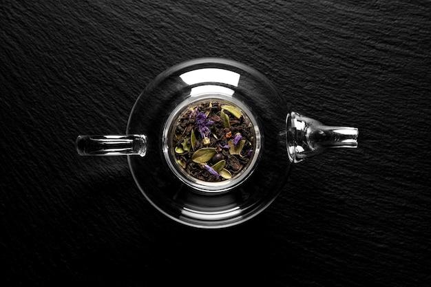 Trockene teeblätter in einer teekanne auf einem stein, flach liegen