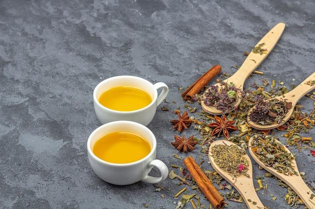 Trockene teeblätter und zwei tassen grüner tee. bio-kräutergetränk