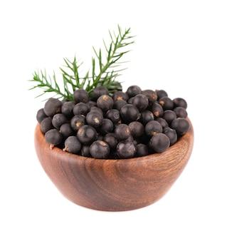 Trockene wacholderbeeren in der holzschale, isoliert. gewöhnliche wacholderfrüchte.