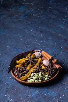 Trockene wärmende indische gewürze für herbst- und wintermahlzeit auf dunkelblauem beton.
