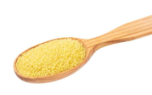 Trockener couscous im hölzernen löffel lokalisiert auf weiß