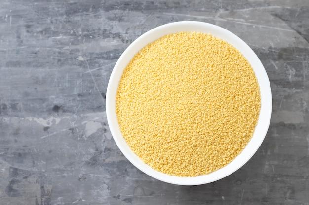 Trockener couscous in weißer schüssel auf keramiktisch