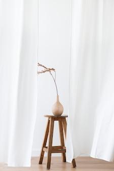 Trockener forsythienzweig in einer holzvase auf einem hocker vor einem weißen vorhang