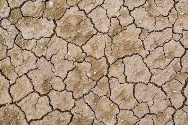 Trockener gebrochener erdhintergrund, lehmwüstenbeschaffenheit