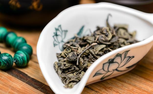 Trockener grüner tee auf holztisch