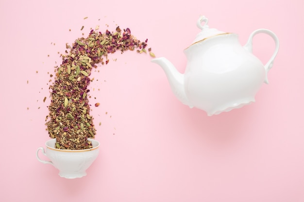Trockener kräutertee, der aus der weißen porzellanteekanne in eine tasse auf rosa gießt. flach liegen. teezeitkonzept.