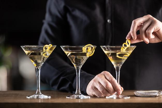 Trockener martini-shortdrink-cocktail mit gin, trockenem wermut und einer zitronenschale als garnitur.