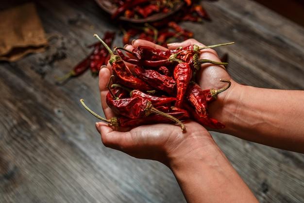 Trockener mexikanischer chilipfeffer der nahaufnahme in den händen über einem holztisch