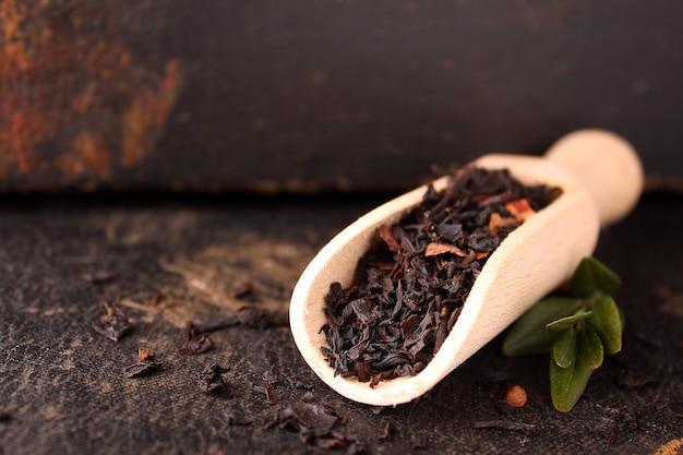 Trockener schwarzer tee auf einem schwarzen hintergrund