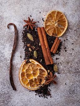Trockener schwarzer tee mit gewürz und orange. selektiver fokus